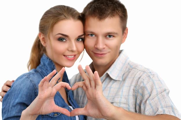 笑顔の美しい少女と白で隔離される手でハートの形を作る彼女のボーイフレンドの肖像画。愛の概念。