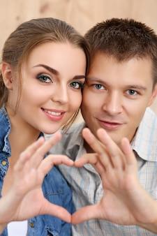 笑顔の美しい少女と彼女のボーイフレンドが自分の手でハートの形を作るの肖像画。愛の概念。