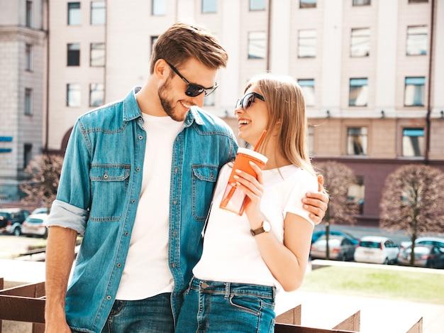 Портрет улыбается красивая девушка и ее красивый парень в повседневной летней одежды. , женщина с бутылкой воды и соломы