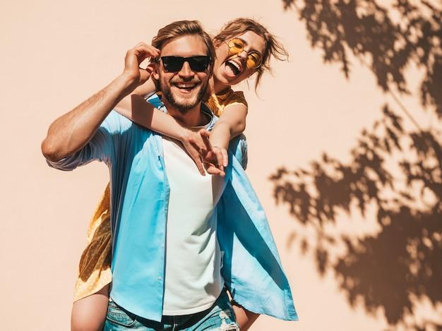 Портрет улыбается красивая девушка и ее красивый парень. женщина в повседневное летнее платье и мужчина в джинсах. счастливая веселая семья. девушки веселятся на улице возле стены