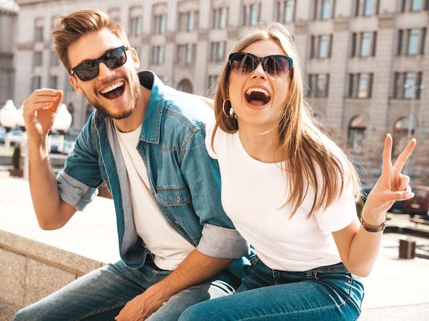 笑顔の美しい少女と彼女のハンサムなボーイフレンドの肖像画。カジュアルな夏のジーンズ服の女性。ピースサインを表示