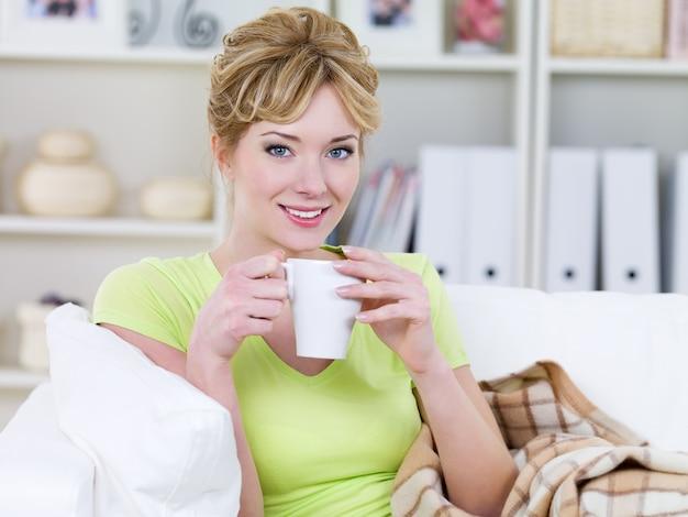 Портрет улыбающейся красивой довольно молодой женщины, пьющей горячий кофе дома - в помещении