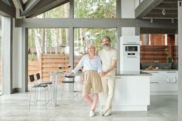 モダンな家のキッチンに抱きしめて笑顔の美しい年配のカップルの肖像画