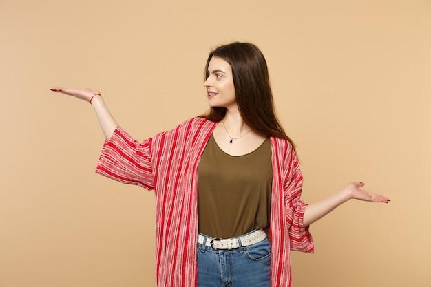 Портрет улыбающейся красивой женщины в повседневной одежде, разводящей указывая руками в сторону, изолированную на пастельных бежевых стенах в студии. люди искренние эмоции, концепция образа жизни. копируйте пространство для копирования.