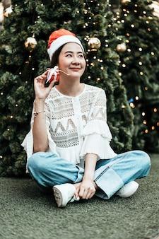 Портрет улыбающейся красивой молодой азиатской женщины с подарком на праздничной рождественской ярмарке
