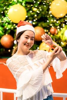 축제 크리스마스 박람회에 선물을 가진 웃는 아름 다운 젊은 아시아 여자의 초상화