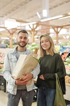 現代のファーマーズマーケットでバッグを持って立っているカジュアルな服装で笑顔の美しい若いカップルの肖像画