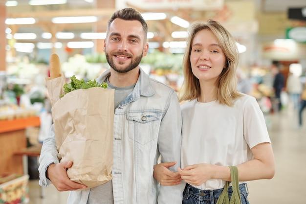 Портрет улыбающейся красивой молодой пары, стоящей с бумажным пакетом на фермерском рынке