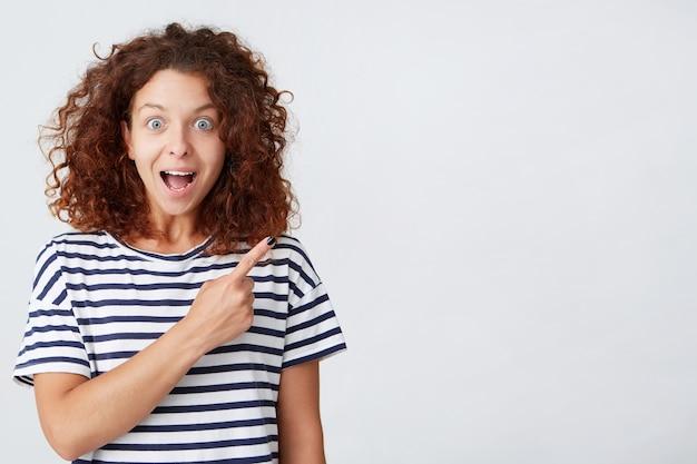 곱슬 머리를 가진 웃는 아름 다운 젊은 여자의 초상화는 스트라이프 티셔츠를 착용