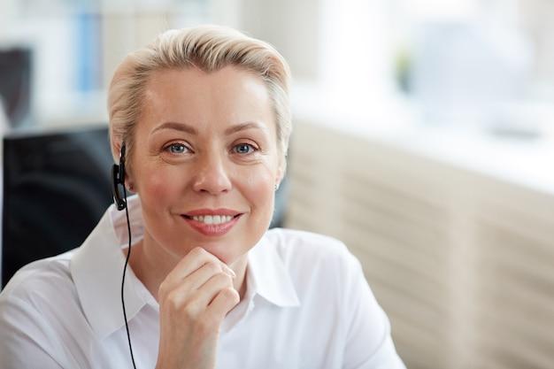 Портрет улыбающейся блондинки в гарнитуре и глядя во время работы в колл-центре службы поддержки