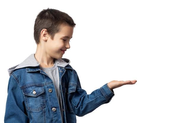 데님 재킷에 웃는 소년의 초상화는 손으로 보여주고 격리 된 흰색 배경에 재미, 그녀를 쳐다 본다