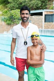 Портрет улыбающегося мальчика, стоящего со своим тренером у бассейна