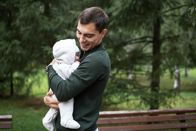 Портрет улыбающегося брюнет-папы в зеленой куртке с ребенком на руках в парке, концепция безусловной любви