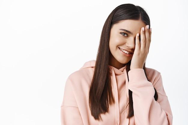 顔の半分を覆って幸せそうに見える笑顔のブルネットの女性の肖像画、自然光メイク、白い壁を身に着けている