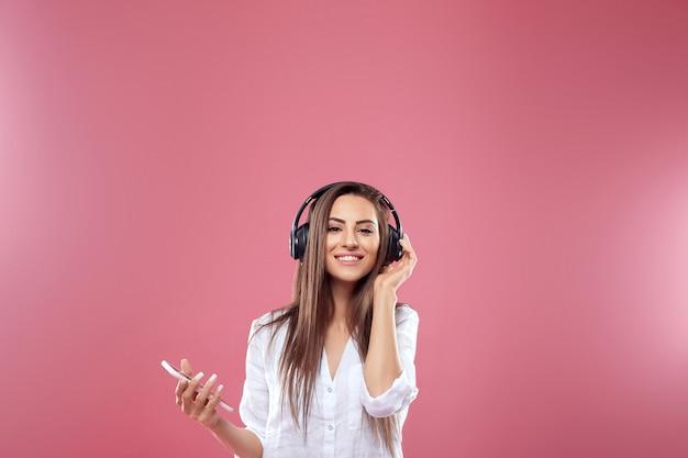 ピンクの背景の上の音楽を聞くスマートフォンとヘッドフォンで笑顔のブルネットの女性の肖像画。女の子はワイヤレスイヤホンを使用しています。