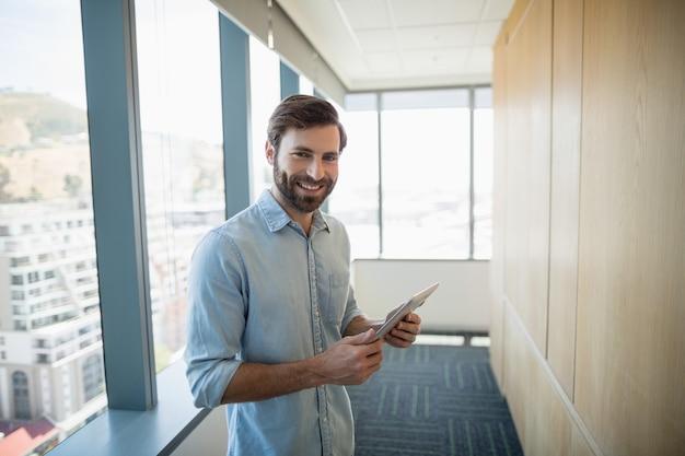 Портрет улыбающегося делового руководителя с помощью цифрового планшета в коридоре