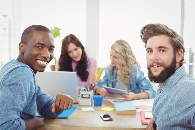 Портрет улыбающегося деловых людей с женщинами, работающих на фоне на столе