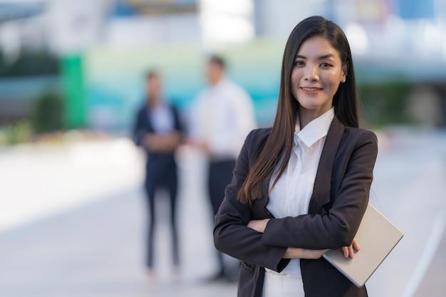 현대 사무실 건물 앞에 서있는 디지털 태블릿을 들고 웃는 비즈니스 여자의 초상화