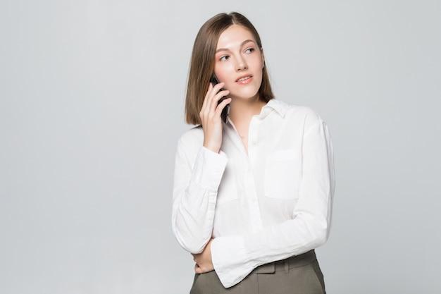 Портрет улыбающейся деловой женщины по телефону, изолированной на белой стене