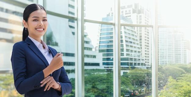 현대 사무실 건물에 서있는 동안 웃는 비즈니스 여자의 초상화