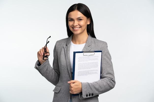彼女の眼鏡を保持し、白い背景の上に孤立して微笑んで、紙のフォルダーと笑顔のビジネス女性の肖像画。職業コンセプト