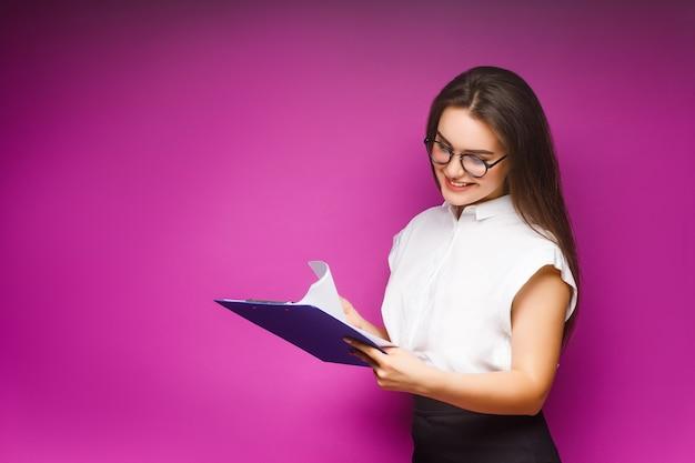 紫に分離された紙フォルダーと笑顔のビジネス女性の肖像画。