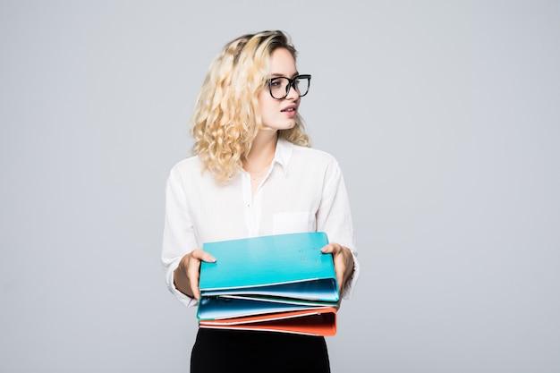 Портрет улыбающейся деловой женщины с бумажной папкой, изолированной на белой стене