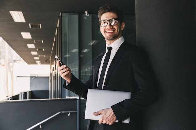 ノートパソコンでガラスの建物の外に立って、携帯電話を使用してフォーマルなスーツに身を包んだ笑顔のビジネスマンの肖像画