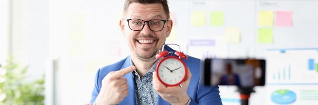 彼の手の時間管理と赤い目覚まし時計を保持している笑顔のビジネスマンの肖像画