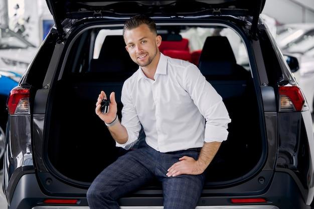ディーラーで自動車のトランクに笑顔のビジネスマンの肖像画