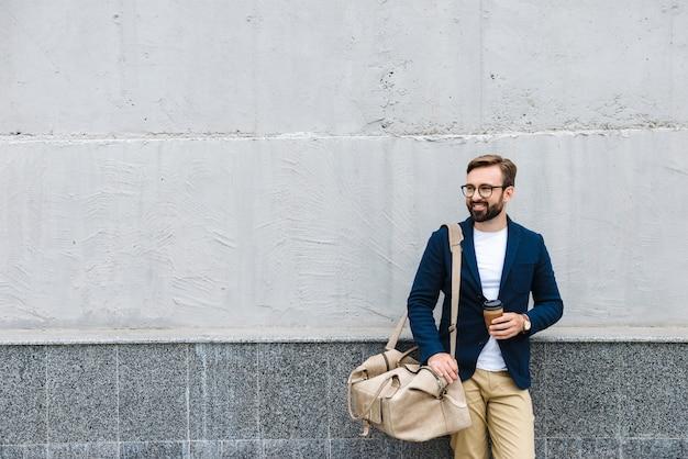 종이 컵을 들고 벽 근처에 서있는 동안 가방을 들고 안경을 쓰고 웃는 사업가의 초상화