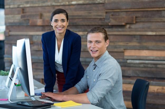 Портрет улыбающихся бизнесменов, работающих на персональном компьютере