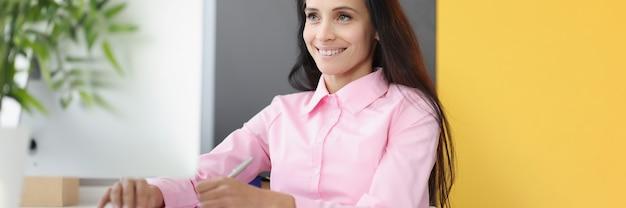彼女の作業テーブルで笑顔の実業家の肖像画