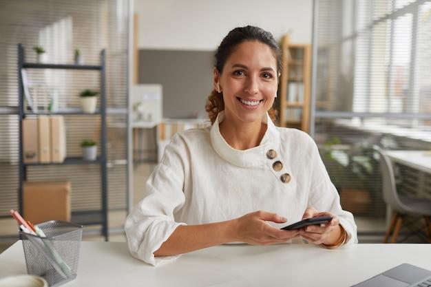 スマートフォンを持って、オフィスの机に座ってカメラを見ている笑顔の実業家の肖像画、コピースペース