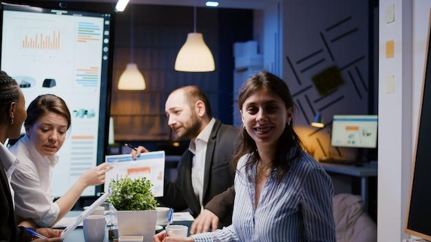회사 회의 사무실에서 책상에 앉아있는 동안 카메라를 찾고 웃는 사업가의 초상화...