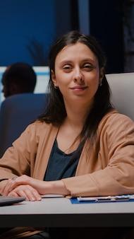 Портрет улыбающейся бизнес-леди, смотрящей в камеру, сидя за столом в офисе запуска бизнеса поздно ночью