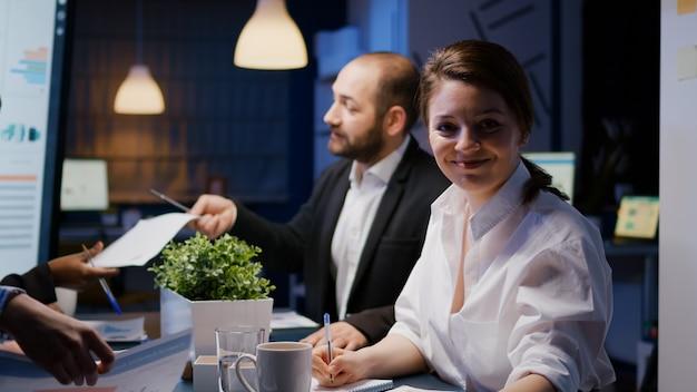 늦은 밤 사무실 회의실에서 초과 근무를 하는 카메라를 바라보고 있는 웃고 있는 사업가의 초상화. 투자 전략을 논의하는 워커홀릭 다양한 다민족 팀워크