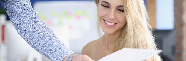 Портрет улыбающейся деловой женщины, коллега которой передает деловой документ