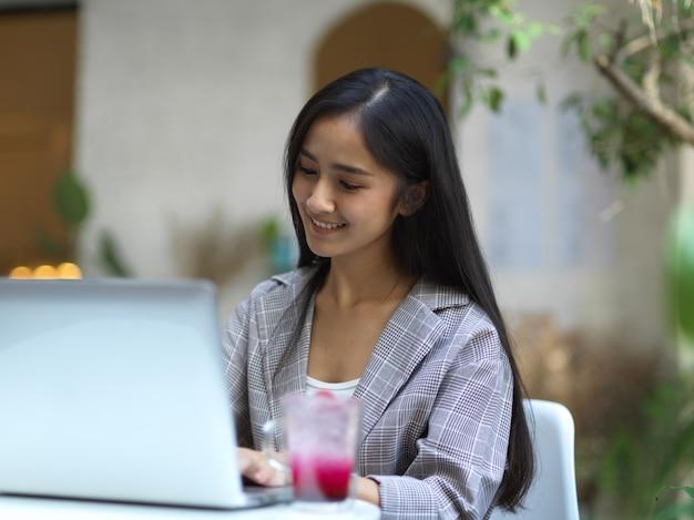 Портрет улыбающейся деловой женщины, работающей с ноутбуком на журнальном столике в саду перед кафе