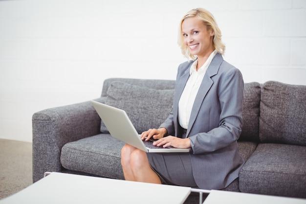 Портрет улыбающегося деловая женщина работает на ноутбуке
