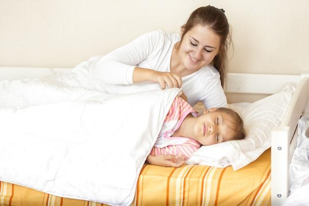娘を毛布で覆う笑顔の慎重な母親のポートレート