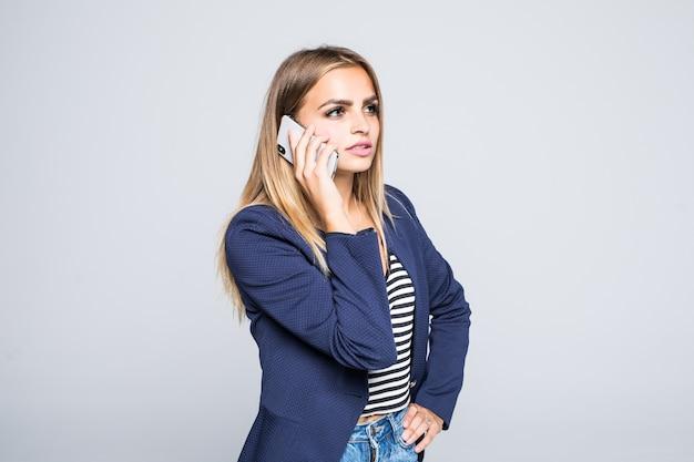 立っている間電話で話している笑顔のカジュアルな女性の肖像画