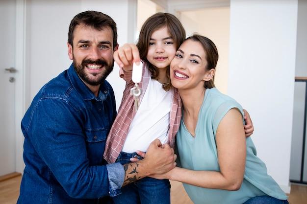 딸이 열쇠를 들고 있는 동안 새 집으로 이사하는 백인 가족의 초상화.