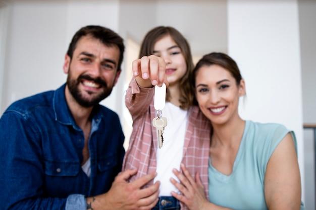 그들의 새 집의 열쇠를 들고 딸과 함께 웃는 백인 가족의 초상화.