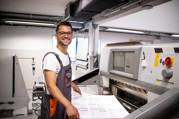 印刷工場で紙切断機のそばに立っている笑顔の白人オペレーターの肖像画。