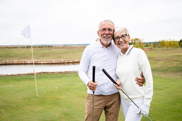 Портрет улыбающейся кавказской старшей пары, держащей гольф-клубы и стоящей на курсе.