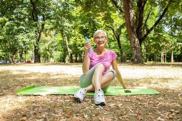 자연에서 실행 훈련을 준비 하는 웃는 백인 여자의 초상화.