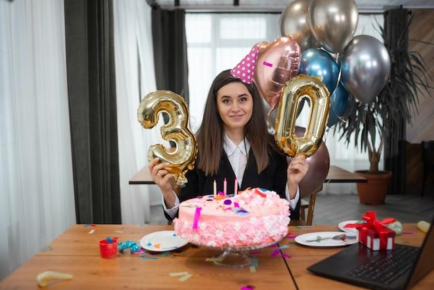 웹캠에 테이블, 생일 케이크와 번호 30에 앉아 웃는 백인 여자의 초상화.