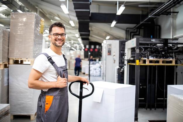 新しい紙を現代の印刷機に入れる準備ができている笑顔の白人労働者の肖像画。