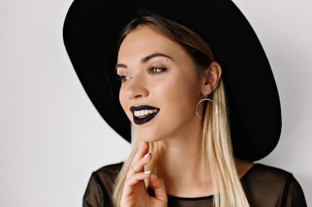검은 립스틱과 검은 모자와 웃는 매력적인 여자의 초상화